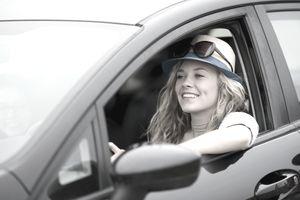 Smiling young woman behind the wheel of a car