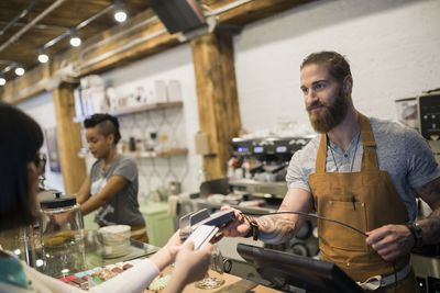 Customer paying barista with credit card in cafe