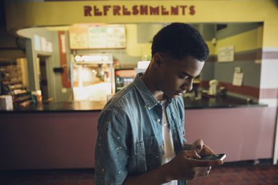 Young man using smart phone in front of a refreshments counter