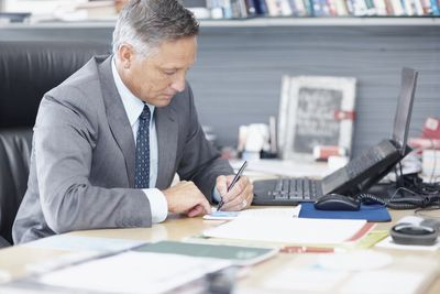 Shareholder at a desk with a laptop and writing on a document