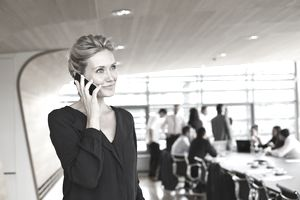 Businesswoman holding phone in conference room