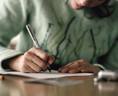 Woman writing on paper, close-up