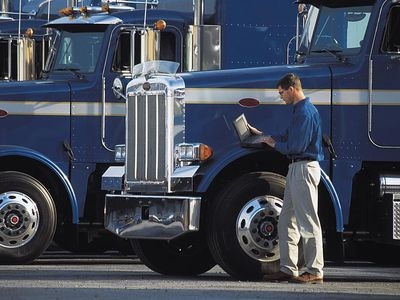 Man using laptop to direct product supply chain movements