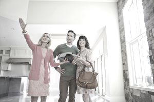 Couple with a real estate agent looking at a short sale house.