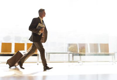 Business traveler walking through the airport with a rolling suitcase.