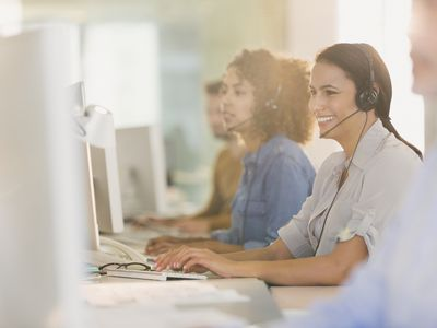 Smiling businesswoman with headset working at computer in office