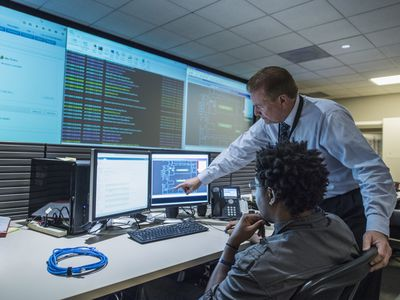 Colleagues working on cyber security issues in control room