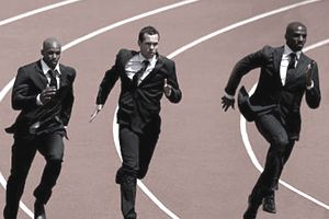 Three men in business suits competing by running on a track