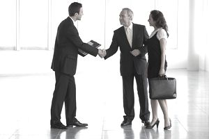 a businessman accompanied by a colleague and shaking hands with another businessman