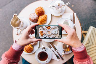 A blogger takes a photo of a lavishly laid breakfast table using a smartphone camera.