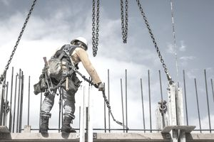 Worker holding chain at construction site precariously balanced on a beam high in the air.