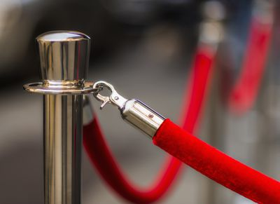 Red velvet rope cordoning off an exclusive area, representing the concept of exclusivity.