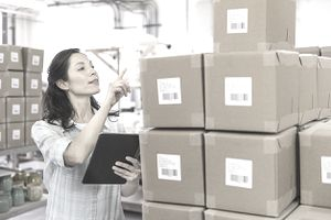 Woman taking Inventory in an optimally laid out warehouse full of cardboard boxes.