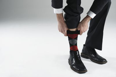 Man pulling up red and grey argyle sock in suit with dress shoes