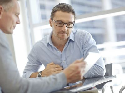 Two businessmen discussing a pro bono document at a table in an office.