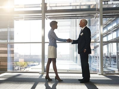 Young Woman Shaking Hands With a Mature Man
