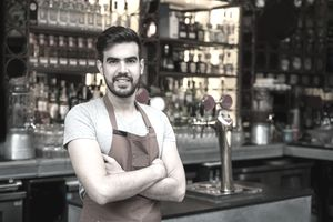 A bartender standing in front of a bar