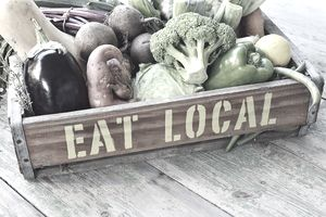 """Eat local"" printed on a crate containing an assortment of vegetables."