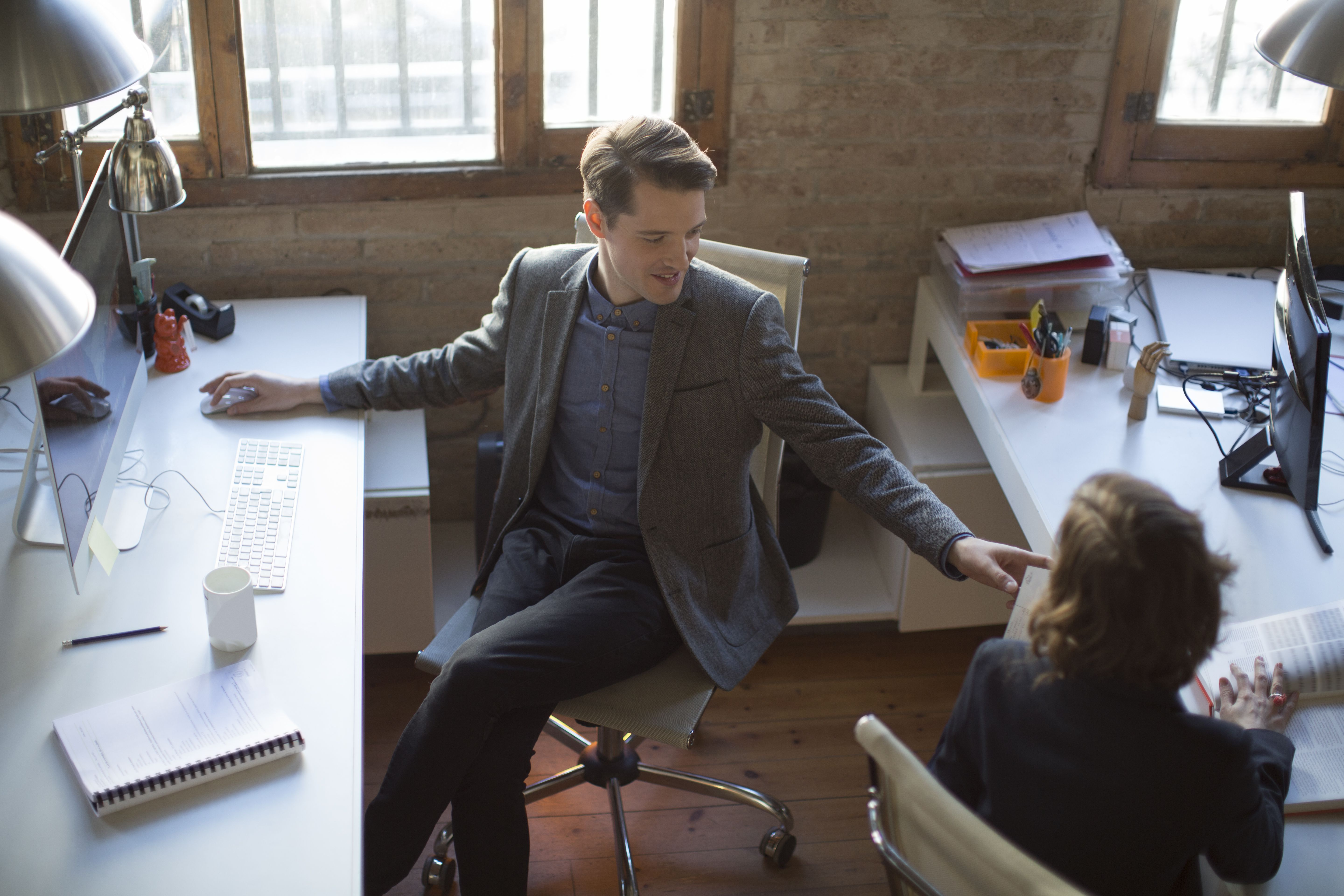 Two people working and interacting at desks in a co-working space