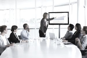 Group of people looking at data displayed on a monitor during a presentation