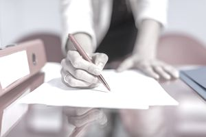 woman editing writing with red pen
