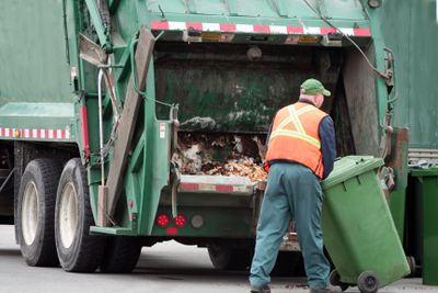 Waste management worker positions green bin on the automatic dumper at the back of truck.