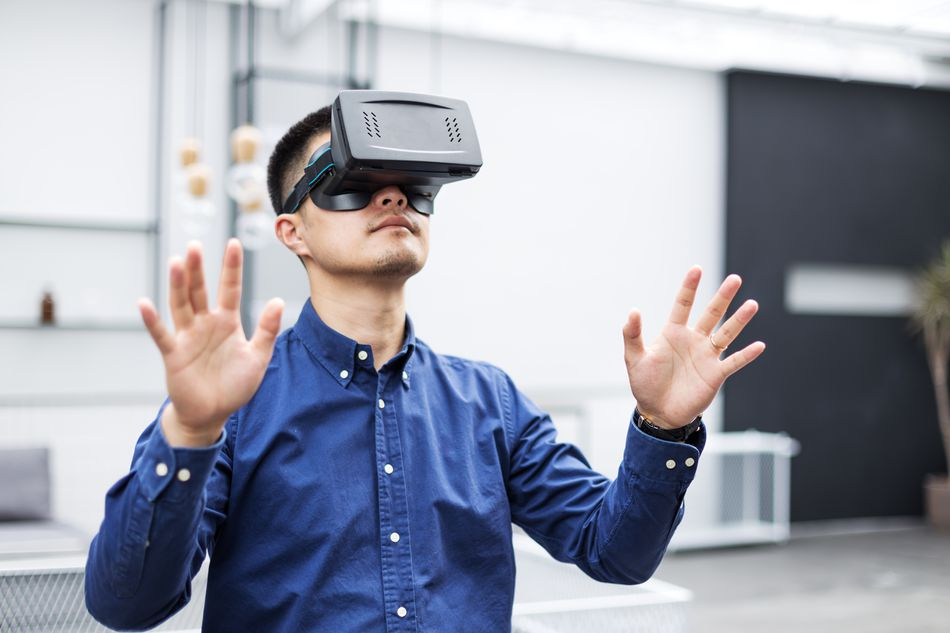 young asian man with VR in modern cafe