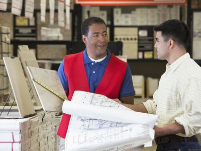 Worker and contractor reading blueprints in home improvement store