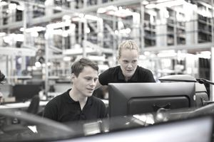 Two employees at a computer in a large logistics warehouse benchmarking the product flow.