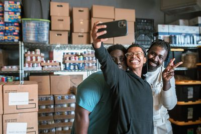 Volunteers at a community food bank with phone posing for selfie