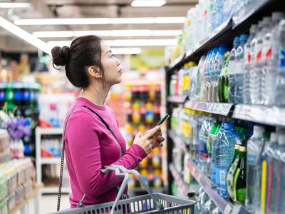 asian female using smart phone while shopping in supermarket