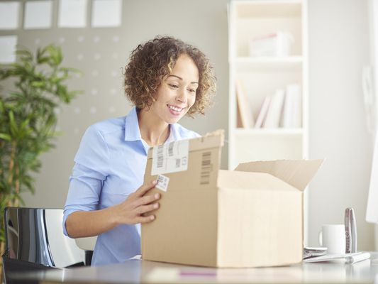 Woman unpacks back in her home office