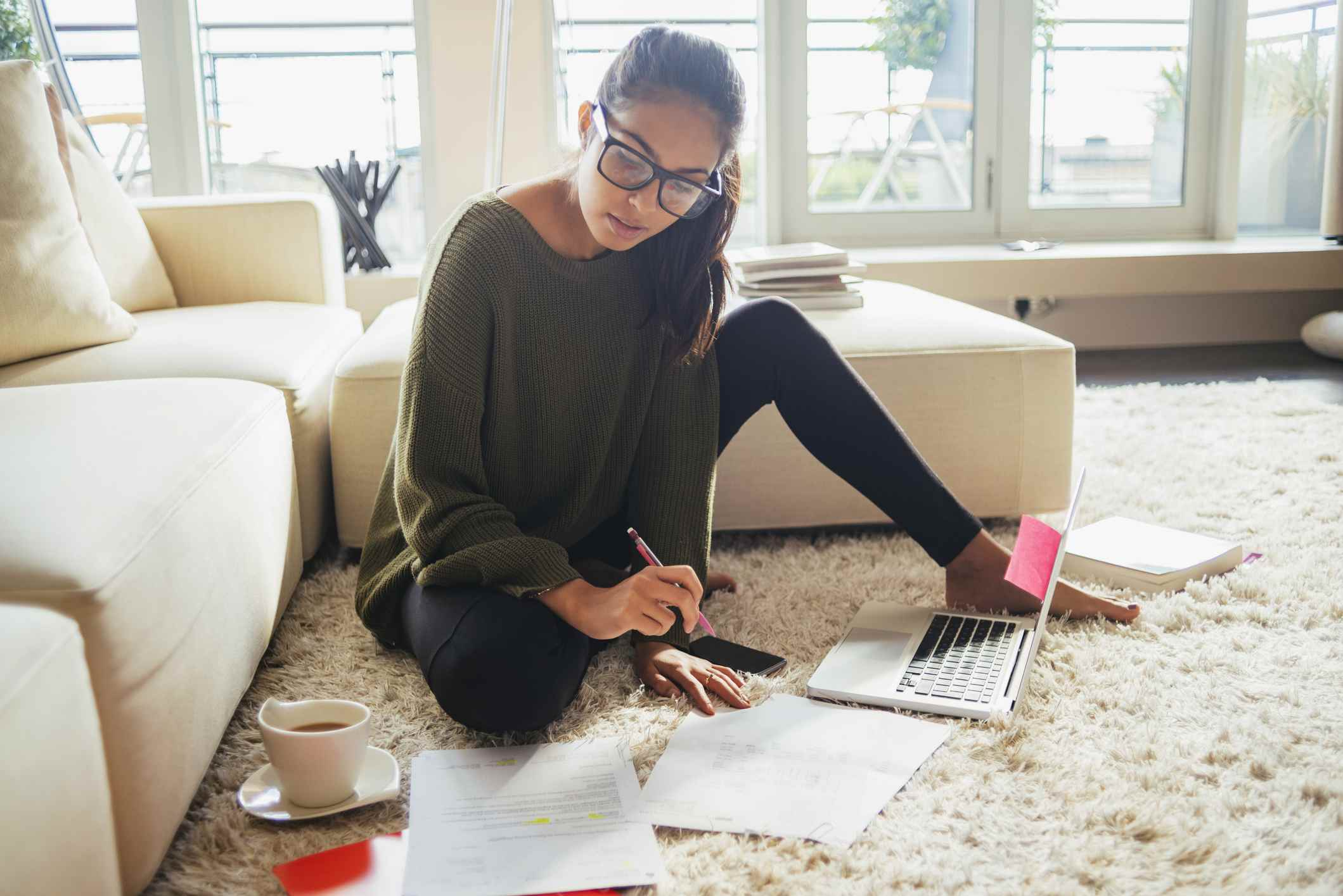A young woman writes an abstract on a laptop surrounded by her notes and research. Learn how to write an abstract here.