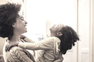 Playful African American mother and daughter having fun at home.
