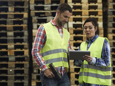 Two warehouse workers standing in front of wood pallets and looking at a tablet
