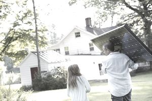 Man carrying a solar panel to his house.
