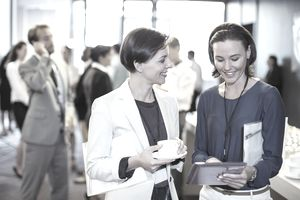 Two smiling women, talking in lobby of conference center during coffee break