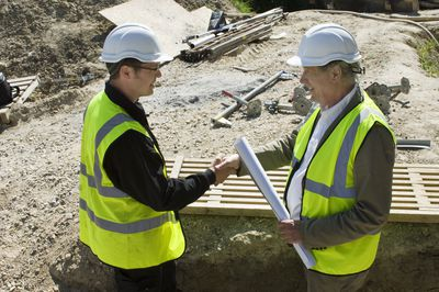 Contractor shaking hands with an engineer before he ask for a time extension on the construction contract.