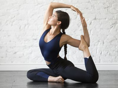 Young woman practicing yoga, stretching in One Legged King Pigeon exercise,