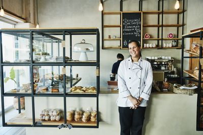 Bakery owner standing in front of counter in shop