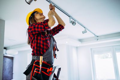 A woman doing repairs to ceiling track work