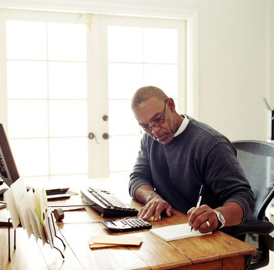 Man sitting a his desk in front of a computer writing in a notepad