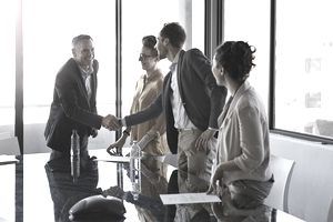 Businesspeople shaking hands after selling a company in a high rise office space.