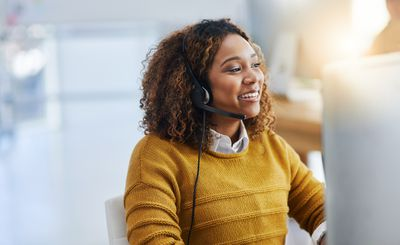 woman sitting at a desk with a headset on, smiling