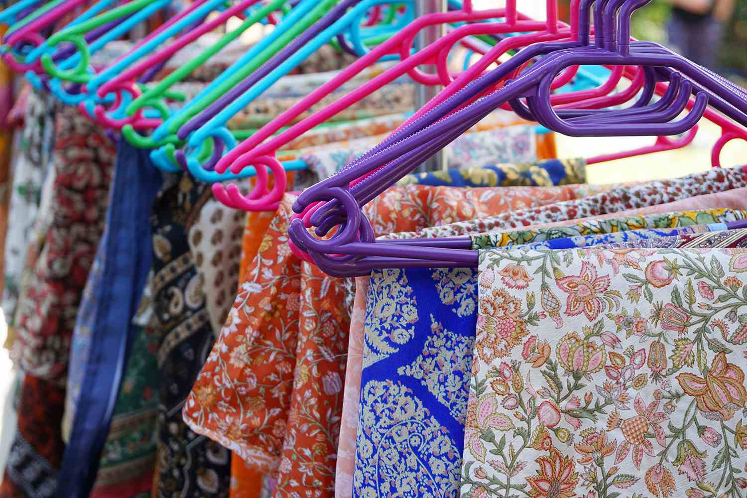 Close-Up Of Colorful Patterned Clothes Hanging On Coathangers At Market