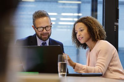 A man and woman look at a laptop to review insurance options