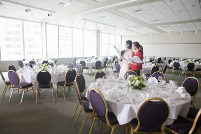 Businesswomen discussing place settings in banquet room
