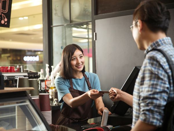 Restaurant cashier accepting payment from a customer