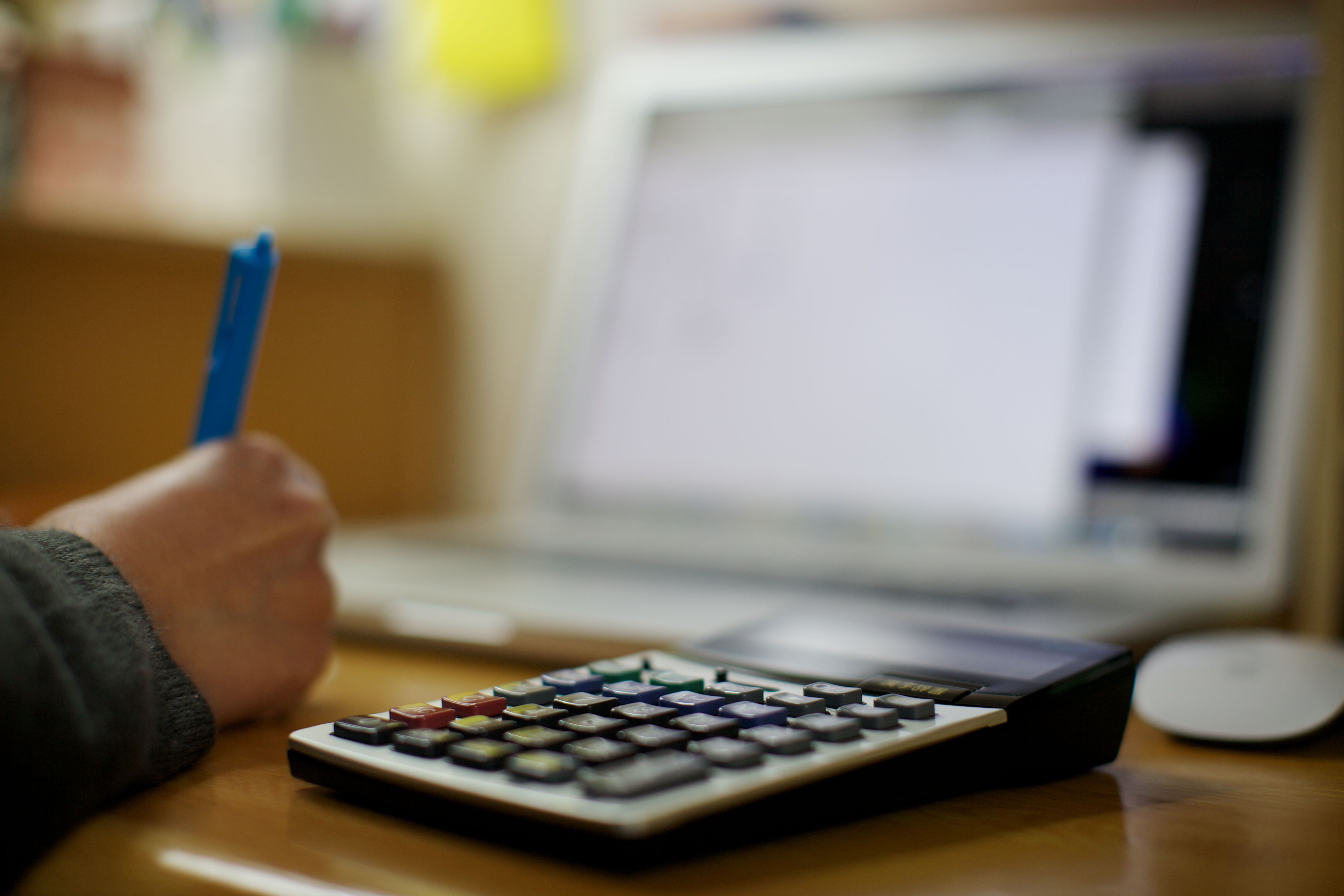 Accountant working at desk, calculator in focus