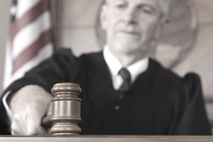 Closeup of a judge in a courtroom banging a gavel